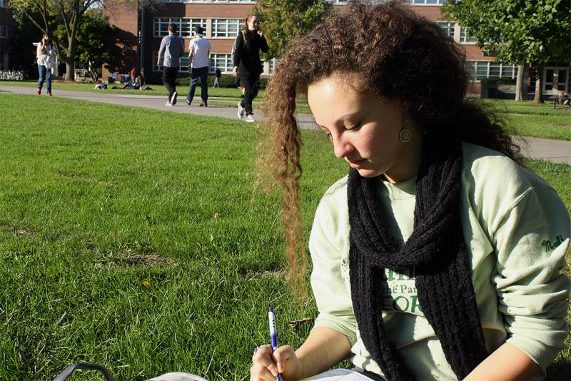 Mali Golomb-Leavitt, a freshman psychology major, fashions a long, knitted scarf on the quad as she studies.