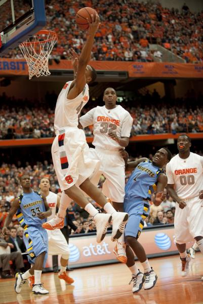 Wes Johnson (4) recovers a defensive rebound against Marquette. Syracuse went on to win 76 - 71. Photo: Andrew Burton