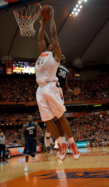 Syracuse's Arinze Onuaku slam dunks despite Henry Sims' attempt to block his shot. Onuaku finished the night with 6 points. Photo: Andrew Burton/The NewsHouse